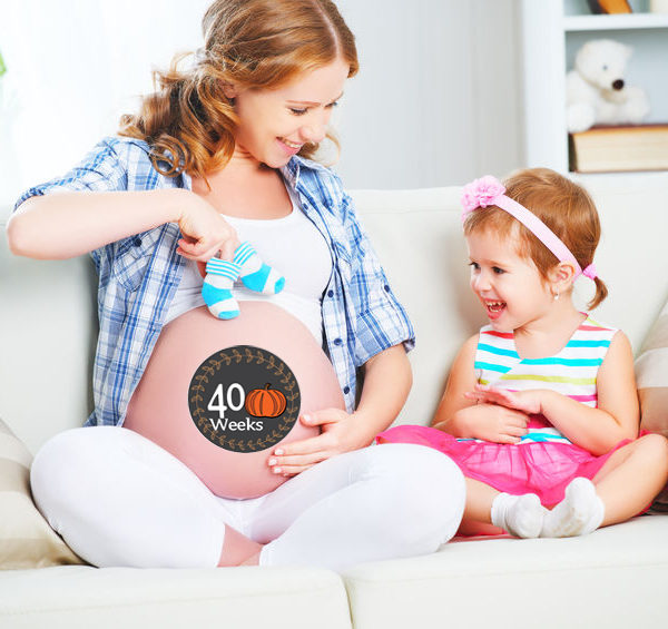 46637417 - happy family pregnant mother and child daughter preparing clothing for newborn baby